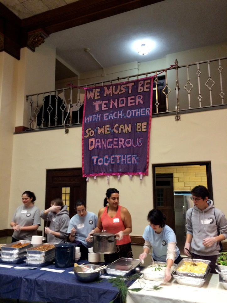 """At the 17th Annual Summit Against Racism, volunteers prepare to serve foods to the large crowd in attendance. A banner reads """"We must be tender with each other so we can be dangerous together."""" I couldn't agree more. The event was held at the East Liberty Presbyterian Church in East Liberty. Photo courtesy of Joyce Wagner."""