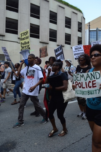 "A group of black - appearing people marching, one person is holding the megaphone for a woman walking next to them who is chanting. A woman in the forground holds a sign that says ""Demand Police Accountability"". There are other people in the background marching with signs."