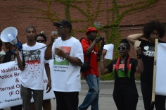 Black-appearing people of color standing in a group, looking determined, some using microphones and megaphones to speak. some with arms raised and or holding up signs. one person using a camera to photograph. in the background is a red brick wall covered with green ivy growth.