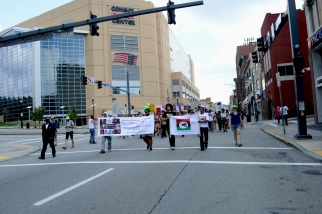 a multiracial group of people walks through the lower hill-uptown down fifth ave, the front of the marching group coming through a crosswalk carrying two signs. these signs are not very visible from this distance but one states 'national mobilization against police brutality and the fraternal order of police'. the crowd of people behind the two front banners are carrying various signs of protest. in the background is the consol energy center.