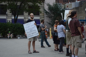 "A mostly white-appearing group stands at the back of a crowd in downtown Pittsburgh. Some bushes, trees, and a building with purple awnings are visible in the background. A few people hold signs facing right, probably towards a speaker. A white-appearing person with a short beard and glasses faces the camera with a sign held to their chest. The sign is white with black marker writing, and it reads: ""DOJ: STOP COPS AND VIGILANTES FROM MURDERING OUR BLACK BROTHERS & SISTERS."""