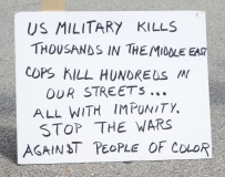 "Close-up of a white poster-board sign with writing in black marker. The sign reads: ""US MILITARY KILLS THOUSANDS IN THE MIDDLE EAST. COPS KILL HUNDREDS IN OUR STREETS... ALL WITH IMPUNITY. STOP THE WARS AGAINST PEOPLE OF COLOR."""