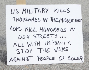 """Close-up of a white poster-board sign with writing in black marker. The sign reads: """"US MILITARY KILLS THOUSANDS IN THE MIDDLE EAST. COPS KILL HUNDREDS IN OUR STREETS... ALL WITH IMPUNITY. STOP THE WARS AGAINST PEOPLE OF COLOR."""""""