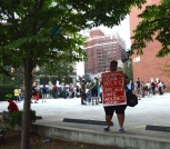 """A black-appearing person wearing sunglasses, blue and white sneakers, and black knee-length pants stands on the curb of a parking lot in downtown Pittsburgh. They face the camera, holding a red sign with white handwriting that appears to be painted. It reads: """"FRATERNAL ORDER OF POLICE ~ 100 YEARS OF STATE VIOLENCE ~ SHAME."""" There is a tree to the left of this person, and a white-appearing person in a red shirt and neon green hat sitting on the curb next to the tree. In the background, a multiracial group of people, including some with bikes, stand in a crowd and appear to be listening to a speaker. Some large brick downtown buildings are also visible in the background."""