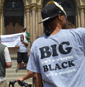 """folks listening to a speaker, a Black appearing person, who is standing atop the steps of a church. behind the speaker, a banner being held out that states """"national mobilization against police brutality and the f.o.p."""". most prominent in the foreground is the back of a Black appearing person's t-shirt that says """"BIG isn't a weapon. BLACK isn't a weapon."""""""