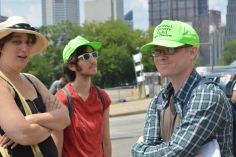 "three white-appearing people standing together, two wearing bright neon green hats that read ""national lawyers guild - legal observers"". they are standing among parking lots and construction signs in the background. in the distance the buildings of downtown pittsburgh business district are visible. context, in the general area of the lower hill - turned civic arena development area."