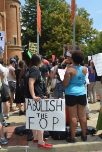 """A multiracial group of people stand in a crowd at Freedom Corner, with their backs to the camera as they listen to a speaker. Many people hold signs in the background. In the foreground, a person with long straight brown hair, a black tee shirt, and a black backpack holds a white sign with large black writing close to the ground. The sign reads: """"ABOLISH THE FOP."""""""