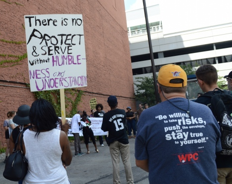 "a gathering of people between buildings. multiracial crowd is listening to a person holding a megaphone. people have signs and expressive t-shirts. most prominently visible is a sign held high stating ""there is no protective and serve without humbleness and understanding""."