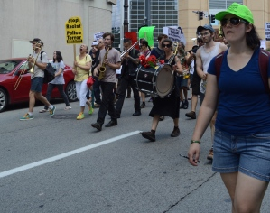 """A multiracial (but predominantly white-appearing) group of marchers walk down a downtown Pittsburgh street. Many of them have instruments -- including a drum, saxophone, and trumpet. Some people carry signs, including a yellow sign with black printed writing that reads, """"Stop Racist Police Terror."""" A white-appearing person with a blue tee shirt, sunglasses, and shoulder-length hair is in the right corner, towards the front of the group. They wear a neon green hat that says """"National Lawyers Guild Observer."""""""