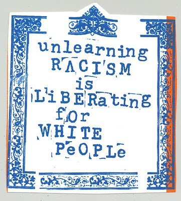 "This is a photo of a sticker that says ""unlearning racism is liberating for white people"". It is in a blue rubber stamp font with an elegant border."